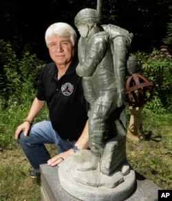 In a photo from June 9, 2017, former Army medic James McCloughan kneels next to a statue presented to him by a fellow soldier in South Haven, Michigan. McCloughan saved the lives of 10 soldiers during the Battle of Nui Yon Hill in May 1969 in Vietnam.