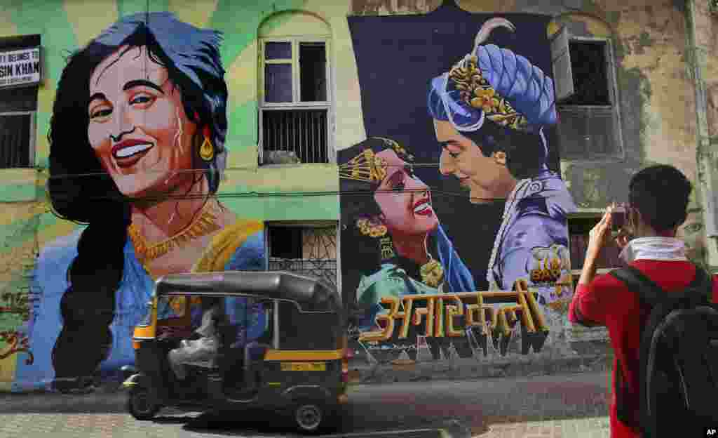 A youth takes a picture of a mural of the Indian movie Anarkali in Mumbai, India.