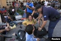 Một người tị nạn Afghanistan ngồi khóc tại cảng Mytilene trên đảo Lesbos của Hy Lạp, ngày 5/9/2015. Hầu hết những người Afghanistan bỏ nước ra đi đã thực hiện những chuyến đi đầy gian nan và nguy hiểm để tìm kiếm một tương lai tốt đẹp hơn ở Âu Châu.