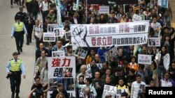 "Demonstrators march during a protest over the disappearance of booksellers in Hong Kong, Jan. 10, 2016. The banner reads, in part: ""Against political kidnapping. ... Demanding the immediate release of the five people from Causeway Bay Books."""