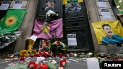 Flags, flowers and candles displayed by members of the Kurdish community are seen in front of the entrance of the Information Centre of Kurdistan where three Kurdish women were found shot dead, in Paris, January 11, 2013.