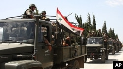 In this photo taken during a government-organized visit for media, Syrian army soldiers ride on their military trucks as they enter the villages near the town of Jisr al-Shughour, north of Damascus, June 10, 2011