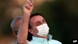 Brazil's President Jair Bolsonaro, who is infected with COVID-19, wears a protective face mask as he attends a Brazilian flag retreat ceremony outside his official residence the Alvorada Palace, in Brasilia, Brazil, Wednesday, July 22, 2020…