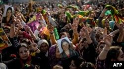 Người Kurd giơ một bức hình chiến binh tử trận trong cuộc chiến với quân đội IS trong ngày lễ tưởng niệm gần biên giới Thổ Nhĩ Kỳ - Syria ngày 27/1/2015.