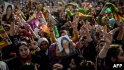 FILE - Kurds celebrating success by Kurd and peshmerga fighters to drive Islamic State militants out of Kobani hold a photo of a fighter killed in the conflict, near the Turkish-Syrian border at Suruc, in Sanliurfa province, Jan. 27, 2015.