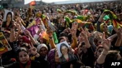 Warga Kurdi merayakan kemenangan pasukannya dan pejuang Peshmerga dalam memukul ISIS ke luar dari Kobani, sambil memegang foto pejuang yang tewas dalam konflik itu (27/1).