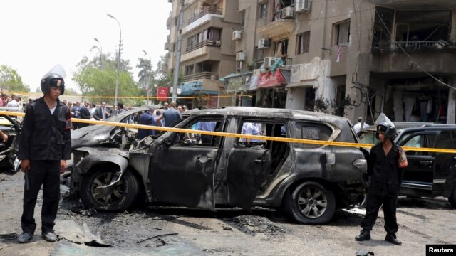 Policemen secure the site of a car bomb attack on the convoy of Egyptian public prosecutor Hisham Barakat near his house at Heliopolis district in Cairo, June 29, 2015.