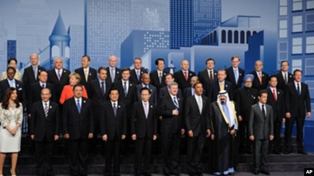 Heads of states and governments and other dignitaries pose for a family picture during the G20 summit at the convention center in Toronto,  27 Jun 2010.