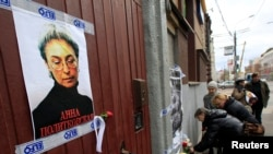 FILE - People lay flowers next to a portrait of slain journalist Anna Politkovskaya near the apartment building where she lived in central Moscow October 7, 2012.