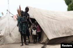 FILE - A woman from the Murle tribe and her children stand outside their tent in Pibor town in Jonglei state, South Sudan, July 18, 2013.