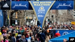 Runners and spectators crowd the finish line on Boyston Street, a day ahead of the 119th Boston Marathon in Boston, Massachusetts, April 19, 2015.