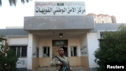 FILE - An armed security guard stands in front of a police station in Benghazi.