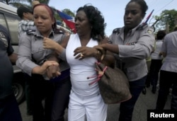 FILE - Berta Soler, leader of The Ladies in White, an opposition group, is detained by Cuban security personnel after a weekly anti-government protest march, in Havana, Sept. 13, 2015.
