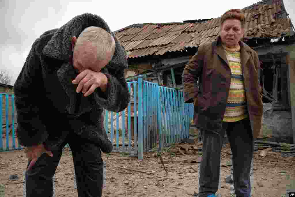Valentina Fedoryak and her husband stand outside their home damaged by shelling in Donetsk, Eastern Ukraine, Wednesday, Nov. 12, 2014.