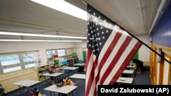 An American flag hangs in a classroom as students work on laptops in a Denver school in Colorado.