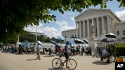 Members of the media set up outside the Supreme Court, Thursday, July 9, 2020, in Washington. The Supreme Court ruled Thursday that the Manhattan district attorney can obtain Trump tax returns while not allowing Congress to get Trump tax and financial rec