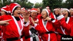 Các thành viên câu lạc bộ Yoga trong trang phục ông già Noel tại một công viên ở Hà Nội.