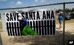 FILE - A man walks past a sign in support of Santa Ana National Wildlife Refuge, home to 400-plus species of birds and several endangered wildcats, at a rally in Mission, Texas, Aug. 12, 2017.