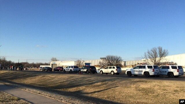 In this photo provided by KWCH-TV, police vehicles line the road after reports of a shooting at an industrial site in Hesston, Kan., Feb. 25, 2016.
