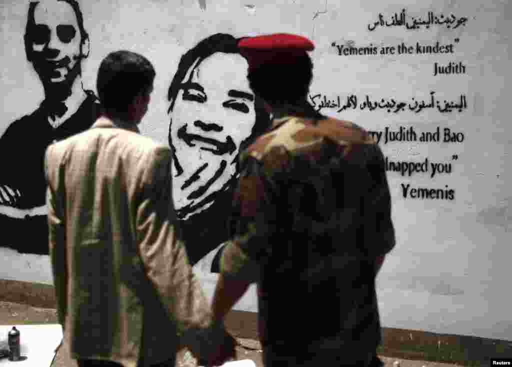 A soldier and a man look at a graffiti depicting kidnapped Dutch journalist Judith Spiegel (C) and her partner Boudewijn Berendsen in Sana'a, Yemen. The couple were abducted in mid-June and are still held hostage by their kidnappers.