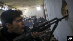 In this Saturday, December 15, 2012 photo, Free Syrian Army fighters aim their weapons as they chant religious slogans during heavy clashes with government forces at a military academy besieged by the rebels north of Aleppo, Syria.