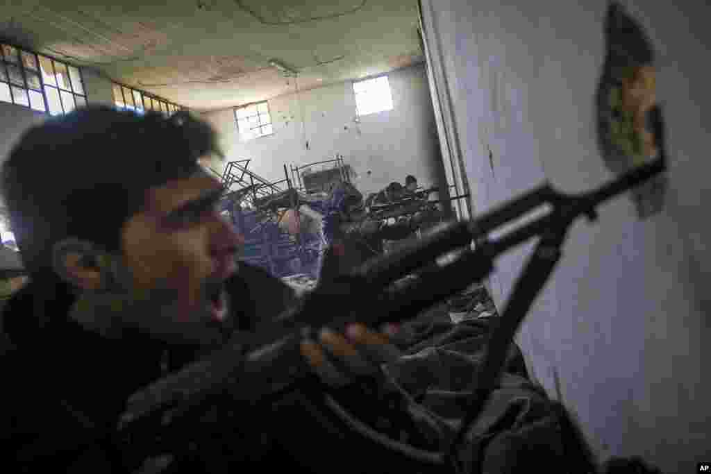 In this Saturday, Dec. 15, 2012 photo, Free Syrian Army fighters aim their weapons as they chant religious slogans during heavy clashes with government forces at a military academy besieged by the rebels north of Aleppo, Syria.