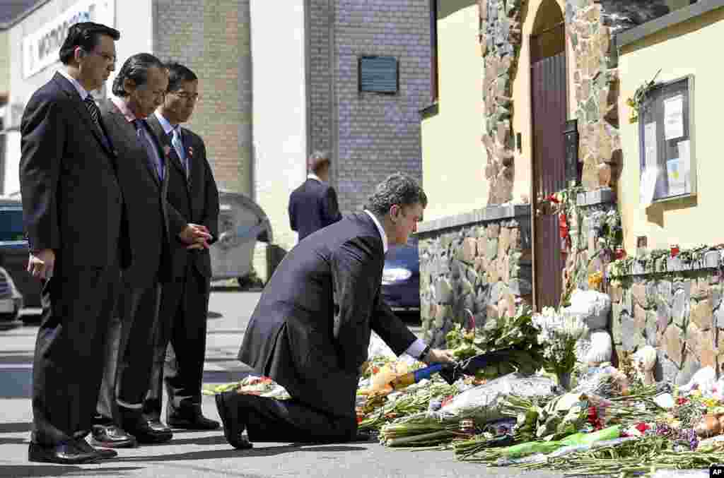 Malaysian diplomats stand as Ukrainian President Petro Porosheko expresses his condolences outside the Malaysian Embassy in Kyiv, July 21, 2014.