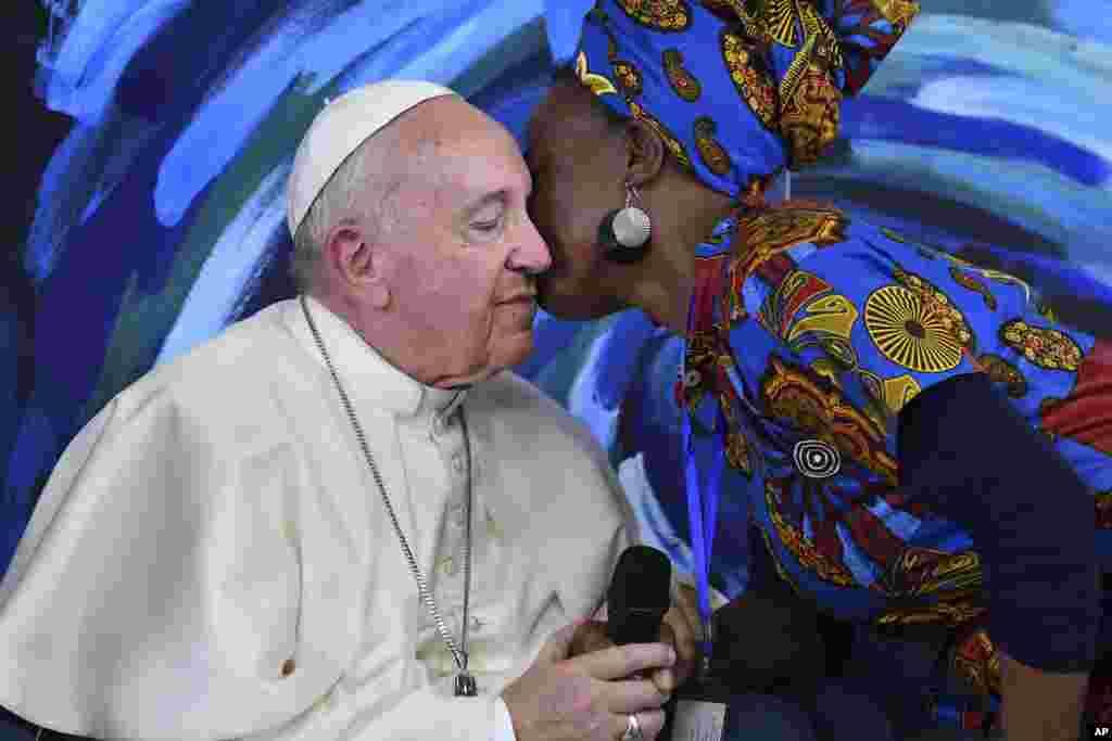 یک زن پاپ فرانسیس را در حاشیه یک کنفرانس در شهر رم می بوسد.