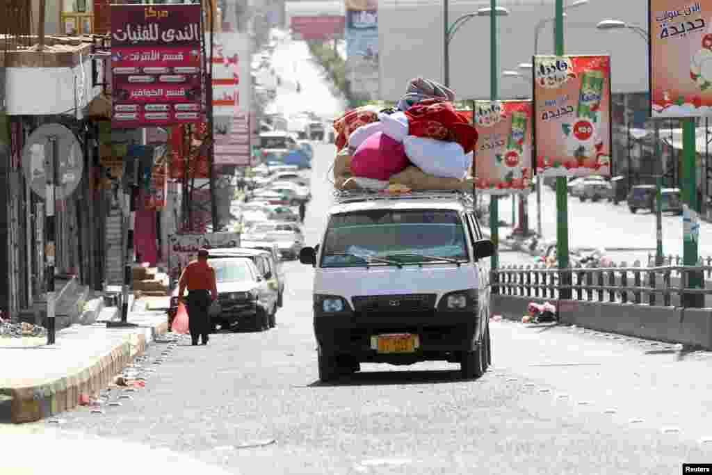 Internally displaced people with luggage ride in a van as they flee from an airstrike on an army weapons depot in Yemen's capital Sana'a.