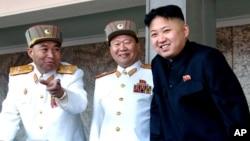 El líder norcoreano, Kim Jong Un, sonríe mientras conversa con dos miliates de la Comisión Militar Central de ese país.
