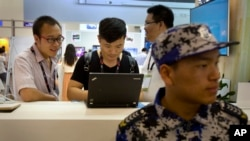 FILE - In this April 29, 2015 file photo, visitors use a laptop computer at a display booth as a security guard stands nearby at the Global Mobile Internet Conference in Beijing. A coalition of international business groups has appealed to China in a letter dated Wednesday, Aug. 10, 2016 to change proposed cybersecurity rules they warn will harm trade and isolate the country.