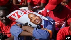 FILE - An opposition party supporter covers his face with a campaign poster of Nelson Chamisa in Harare, July 28, 2018.