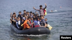 FILE - A dinghy with Syrian and Afghan refugees approaches the Greek island of Lesbos, Sept. 3, 2015. Chile has offered to host families seeking refuge from Syria's civil war.