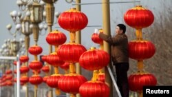 A man hangs lanterns along a street ahead of the Chinese Lunar New Year in Xuchang, Henan province, China, January 15, 2017.