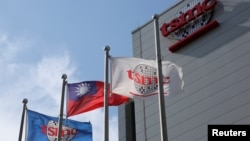 Flags of Taiwan and Taiwan Semiconductor Manufacturing Co (TSMC) are displayed next to its headquarters in Hsinchu, Taiwan October 5, 2017. (REUTERS/Eason Lam)