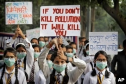 FILE - Schoolchildren hold banners to express their distress at the alarming levels of pollution in the city, in New Delhi, India, Nov. 15, 2017.