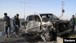 ຕໍາຫລວດອັຟການິສຖານຜູ້ນຶ່ງ ກວດກາສະຖານທີ່ບ່ອນຖືກໂຈມຕີ ດ້ວຍລະເບີດລົດ ຢູ່ໃນແຂວງ Helmand, ວັນທີ 17 ມິຖຸນາ 2013. (AFGHANISTAN - Tags: CIVIL UNREST) - RTX10QPH