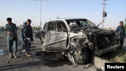 Polisi Afghanistan memeriksa lokasi ledakan bom mobil bunuh diri di provinsi Helmand (17/6). Kepala Polisi setempat, Mohammad Nabi Ilham, dilaporkan selamat dalam serangan bom bunuh diri yang dilancarkan saat dalam perjalanan ke kantornya di Lashkar Gah, Senin pagi tersebut.