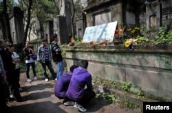 在清明节前,在重庆红卫兵公墓,有学生蹲下阅读碑文。这里埋葬着死于文革中派系武斗的红卫兵(2012年4月2日)