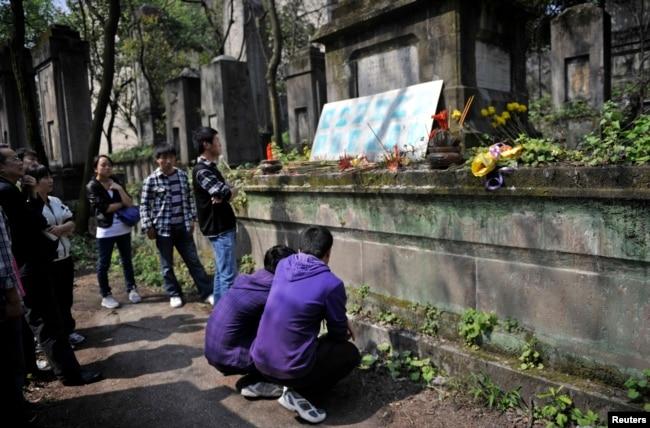 在清明節前,在重慶紅衛兵公墓,有學生蹲下閱讀碑文。 這裡埋葬著死於文革中派系武鬥的紅衛兵(2012年4月2日)