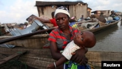 A woman sits in a canoe with her child as the government begins the demolition of homes in Legas.