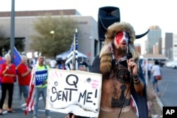 FILE - Jacob Anthony Chansley, who also goes by the name Jake Angeli, a QAnon follower, speaks to supporters of then-President Donald Trump outside of the Maricopa County Recorder's Office, in Phoenix, Nov. 5, 2020.