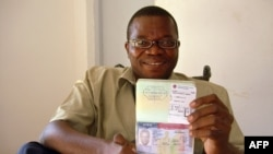 Gabonese opposition and non-government organization member Marc Ona Essangui shows on June 8, 2008 his passport, featuring an exit date and a boarding pass.