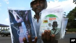 A vendor poses with a fistful of pirated DVDs on sale to passing motorists in central Harare, Zimbabwe, March 17, 2015.