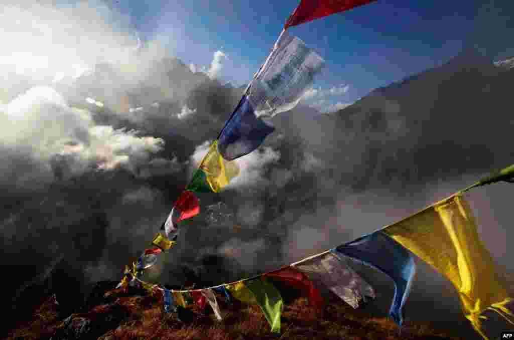 26 tháng 10: Phật tử Tây Tạng cho bay lên trời các tấm vải có lời kinh tại Tengboche, phần đất của Nepal trong vùng núi Himalaya.