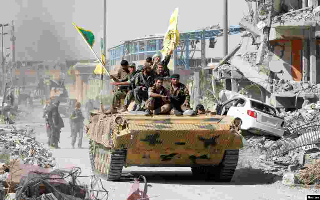 Syrian Democratic Forces (SDF) fighters ride atop a military vehicle in Raqqa as they celebrate victory and the liberation of Raqqa from Islamic State militants.