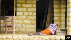 In this Tuesday, Oct. 21, 2014 file photo, a man suffering from the Ebola virus lies on the floor outside a house in Port Loko Community, on the outskirts of Freetown, in Sierra Leone. (AP Photo/Michael Duff, File)