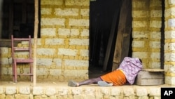 FILE - Man suffering from the Ebola virus lies on the floor outside a house in Port Loko Community, on the outskirts of Freetown, in Sierra Leone.