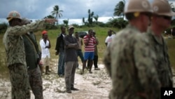 Local workers look on as a team or U.S. Navy engineers prepares the ground for a 25-beds medical facility they are building next to the airport in Monrovia, Liberia, Sept. 27, 2014.