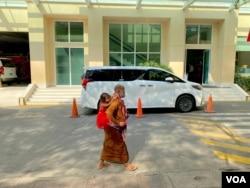 FILE - Two people walk past a vehicle of Prime Minister Hun Sen in Phnom Penh's Calmette hospital in March 2021. (Aun Chhengpor/VOA Khmer)